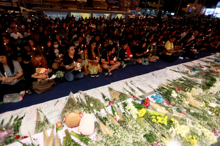 People gather as they pray for victims who died in a mass shooting at Terminal 21 shopping mall in Nakhon Ratchasima, Thailand. -Reuters