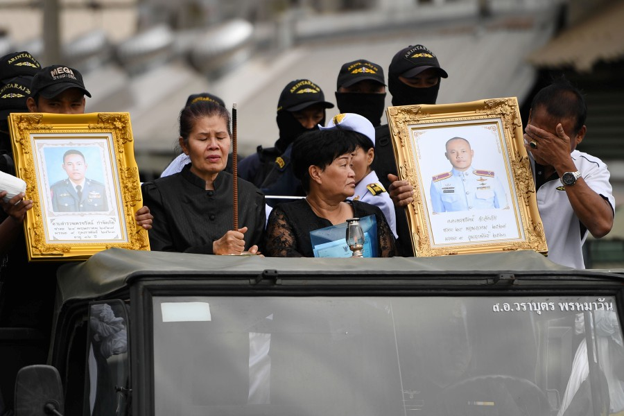 The mother (left in black) of SWAT team member Petcharat Kamjadpai, who was killed in a mass shooting at the Terminal 21 shopping mall, holds incense as the coffin of her son is transported to an air base in the Thai northeastern city of Nakhon Ratchasima. -AFP