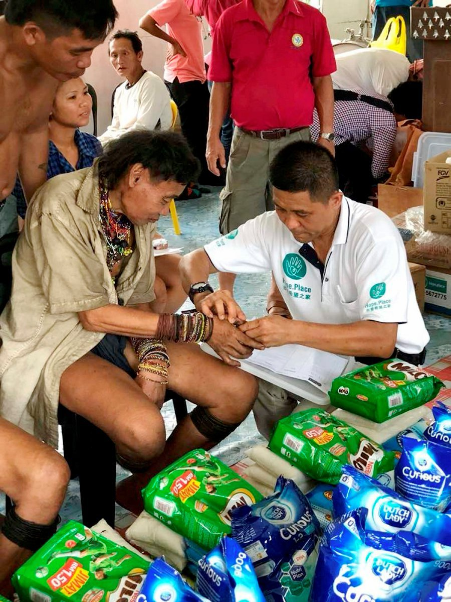 """Hope Place founder Kelvin Wan, assists a recipient to stamp his thumb print as to acknowledge his family has received the donation items from """"Giving Hope, Sharing Love"""" charity project to reach out the Penan community in Ulu Baram."""