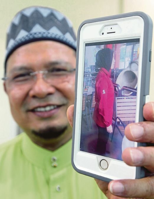 Kelantan Local Government, Housing, Youth and Sports Committee chairman Datuk Abdul Fattah Mahmood showing an example of a suitable uniform for female Muslim workers in fast-food outlets and hypermarkets, in Kota Baru yesterday. Pix by Zaman Huri Isa