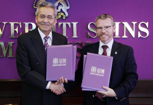 Universiti Sains Malaysia Vice-Chancellor Prof Datuk Dr Omar Osman (left) and Glasgow University Vice Principle and International Dean, Prof Frank Coton pose for a photo following the documents exchange which see USM becoming academic partners. Pix by ZULAIKHA ZAINUZMAN.