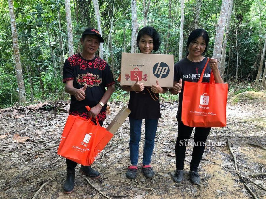 Veveonah (centre) with her brother, Mekvin (left) and their mother (right) receiving goodies from Shopee in July earlier this year. - Pic courtesy of Shopee.
