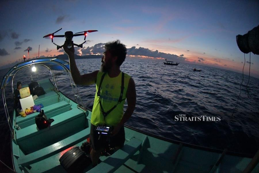 Perhentian Channel Solo Swim 2021 crew Mohd Fahmi Zainal Aripin getting ready to release a drone for video recording.