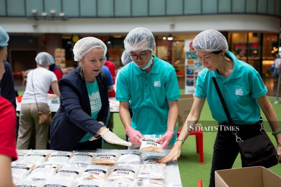 Syazwan (centre) with TLFP's volunteers at the Rise Against Hunger event last year.
