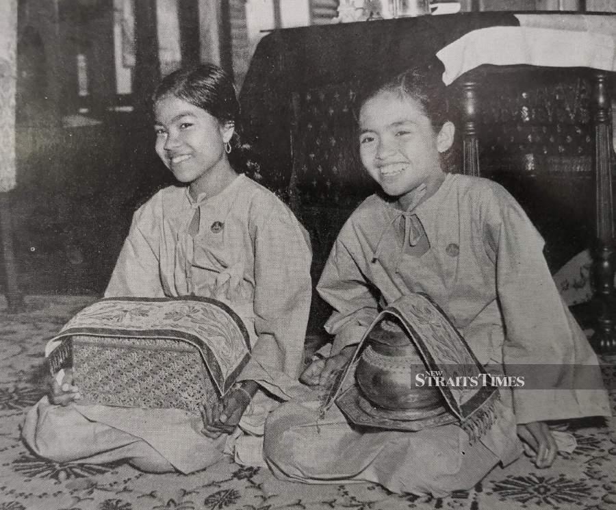 Perak girls elegantly clad in baju kurung.