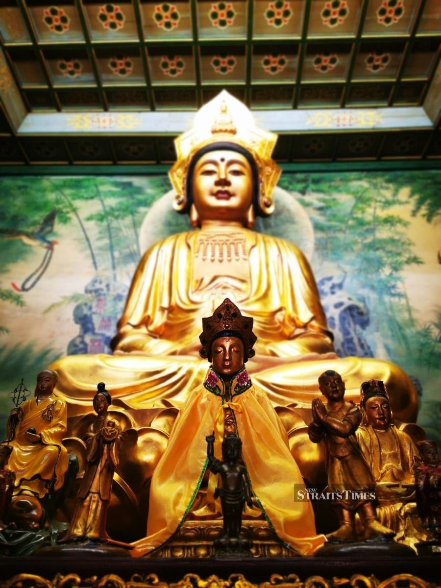 The centre figurine and the one on the far right beneath the life-size Kwan Yin statue are believed to have originated from the old temple.