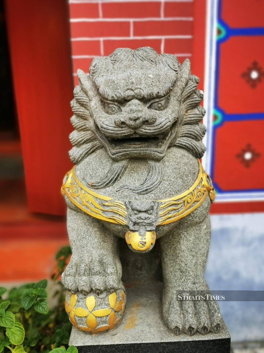 The 'male' stone lion and his golden ball, guarding the temple entrance.