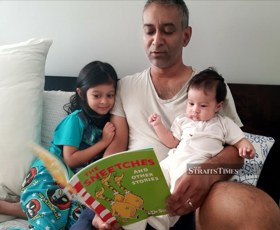 Reading to his two girls is one way that Julian bonds with them.