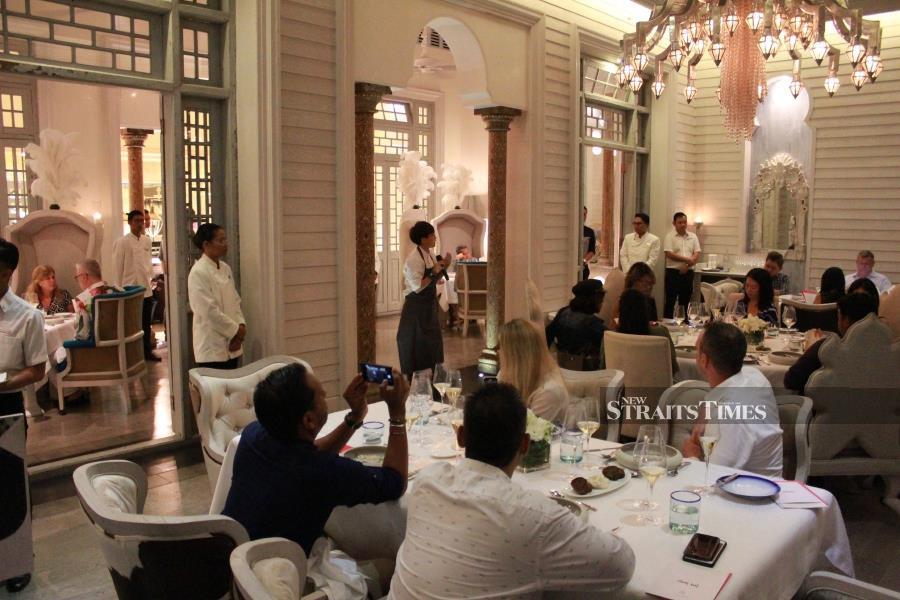 The executive chef explaining her degustation menu at Kayuputi, The St Regis Langkawi's unique destination restaurant.