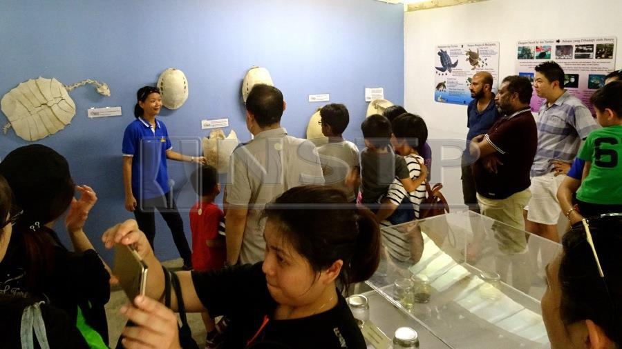 Chan giving a guided tour of the Turtle Gallery in Kg. Pasir Gajah, Kemaman, to participants of the Turtle Discovery Trip.