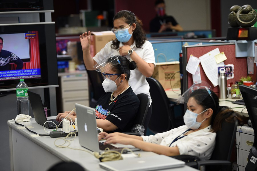 Employees work at their terminals in the ABS-CBN newsroom on the final day of work for most of its staff, at the broadcasting network's headquarters in Manila. - AFP pic