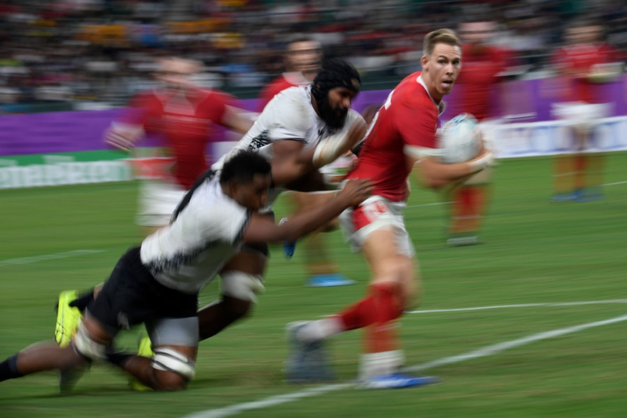 Wales' full back Liam Williams (right) is tackled during the Japan 2019 Rugby World Cup Pool D match between Wales and Fiji at the Oita Stadium in Oita. - AFP