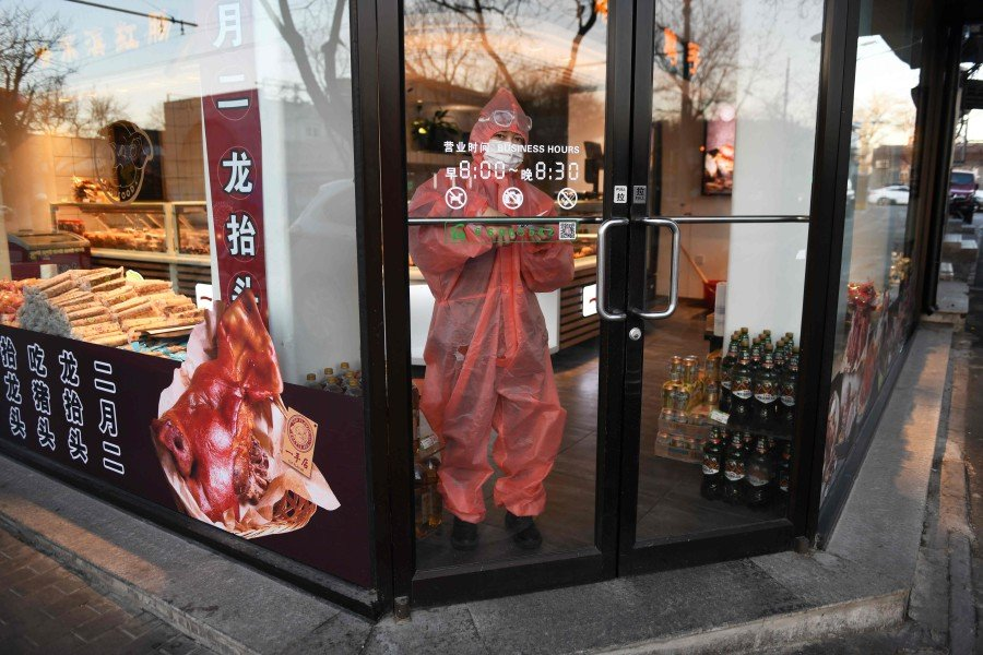 A worker wears a protective suit and face mask as she stands in the entrance of a store in Beijing. -AFP