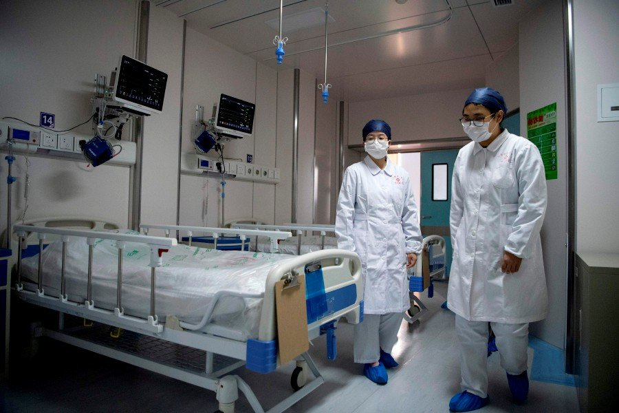 Nurses walk inside a quarantine room at the finished but still unused building A2 of the Shanghai Public Clinical Center, where COVID-19 coronavirus patients will be quarantined, in Shanghai. -AFP