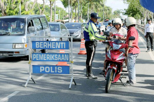 Traffic police checking licence of motorists during Ops Warta in Alor Star, Kedah. Pix by Amran Hamid