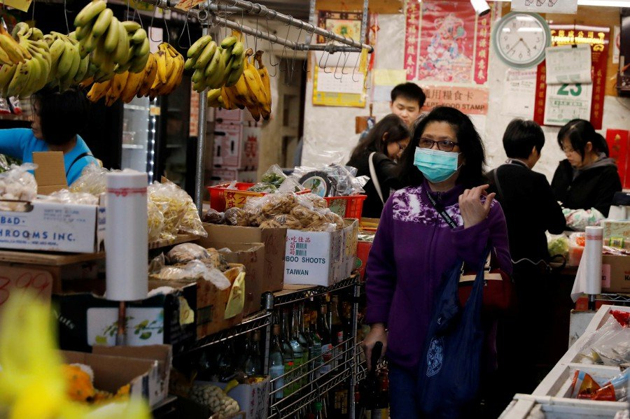 A woman wears a face mask shopping at a market in the Chinatown section of San Francisco, California. -Reuters