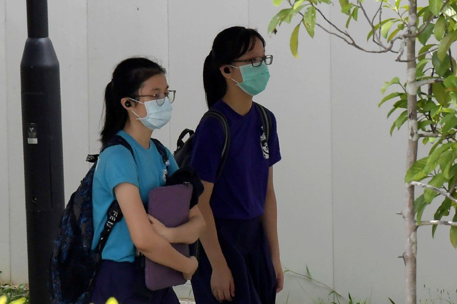 Students wearing face masks, as a preventive measure against the COVID-19 novel coronavirus, walk home from school in Singapore. - AFP pic