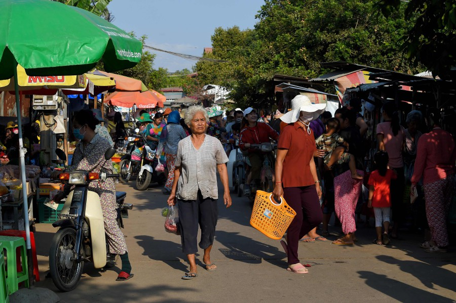People walk in a market, as crowds still gathered in busy places amid the COVID-19 coronavirus, in Phnom Penh. -AFP pic
