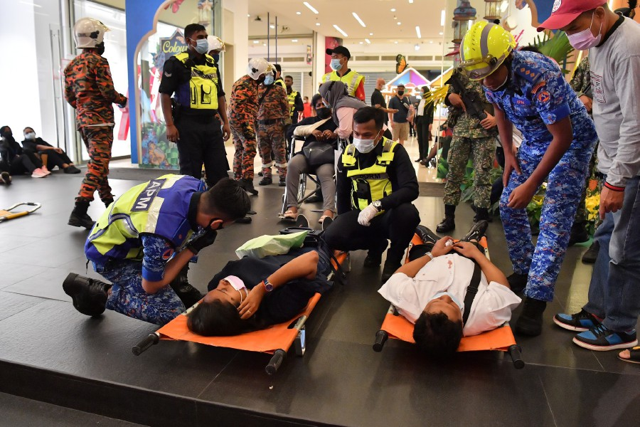 Paramedics attending to the injured passengers before they were taken to the hospital. -- Pix: Bernama