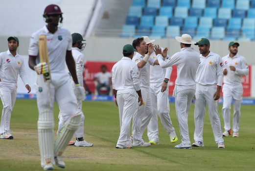 Pakistani spinner Yasir Shah (centre) celebrates with teammates after taking the wicket of West Indies captain Jason Holder (left). AFP